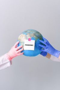 latex gloves holding globe with note about COVID