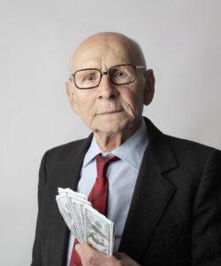 elderly man holding money and life savings