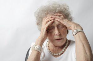 elderly woman holding her head like brain hurts