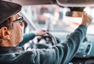 Senior man with hat and eyeglasses adjusting rear mirror while sitting in his car. Other hand on steering wheel. Picture taken from back seat.
